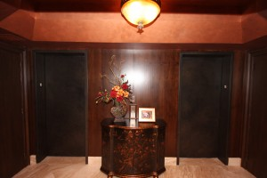 I skinned the entry elevator doors with walnut finish, venetian plastered the ceiling and added a beautiful entry chandelier.