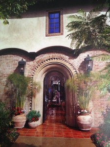 Use of several elements:  Arches, brick, tile, and carriage lights-makes for a welcoming home